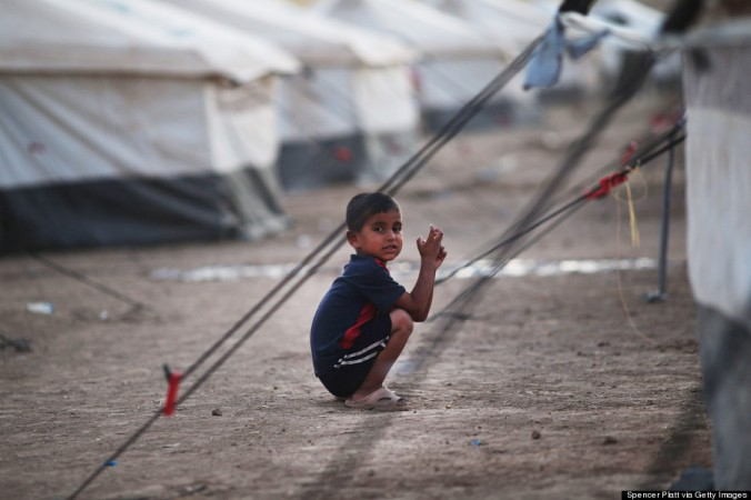 KALAK, IRAQ - JUNE 24:  An Iraqi child pauses in a temporary displacement camp for Iraqis caught-up in the fighting in and around the city of Mosul on June 24, 2014 in Kalak, Iraq.Tens of thousands of people have fled Iraq's second largest city of Mosul after it was overrun by ISIS (Islamic State of Iraq and Syria) militants. Many have been temporarily housed at various IDP (internally displaced persons) camps around the region including the area close to Erbil, as they hope to enter the safety of the nearby Kurdish region.  (Photo by Spencer Platt/Getty Images)