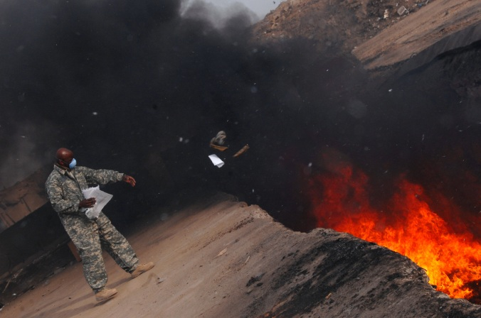 Master Sgt. Darryl Sterling, 332nd Expeditionary Logistics Readiness Squadron equipment manager, tosses unserviceable uniform items into a burn pit, March 10. The 332 ELRS has a central collection point that can be used by service members and Department of Defense civilians; unserviceable uniform items are burned. Sergeant Sterling is deployed from Luke Air Force Base, Ariz.